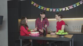 Women clincking glasses at home birthday party. Cheerful females laughing, communicating while pouring champagne celebrating anniversary in festively decorated stock video footage