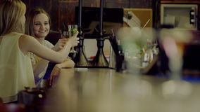 Women clink glasses. Two beautiful young smiling women clinking glasses sitting at a bar counter stock footage