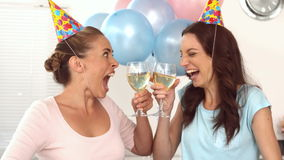 Women clinking their flutes of champagne celebrating a birthday. With party hats party horn and balloonss in slow motion stock video