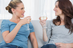 Women clinking their wine glasses while sitting on the sofa Royalty Free Stock Photos