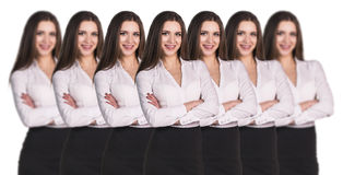 Women clones standing in a row. Group of business woman clones standing in a row Royalty Free Stock Images