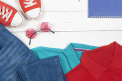 Women clothing set and accessories on a rustic wooden background. Sports T-shirt and sneakers in bright colors. Top view Royalty Free Stock Photos