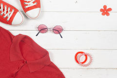 Women clothing set and accessories on a rustic wooden background. Sports T-shirt and sneakers in bright colors. Top view Stock Image