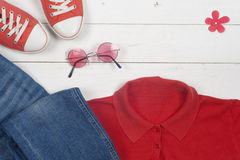 Women clothing set and accessories on a rustic wooden background. Sports T-shirt and sneakers in bright colors. Top view Stock Photos