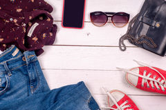 Women clothing set of cool stuff and accessories on light background. Top view. Stock Images