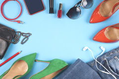 Women clothing set, set of cool stuff and accessories on light blue background. Top view. Stock Image