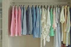 Women cloths hanging in wooden wardrobe royalty free stock photos