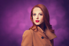 Women in coat. Redhead woman in coat on vilolet background Royalty Free Stock Photography