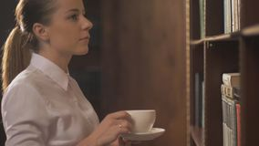 Women with coffee cup. Female college student taking book from shelf in library. lead hand on the shelves with books stock video footage