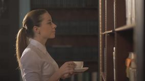 Women with coffee cup. Female college student taking book from shelf in library. lead hand on the shelves with books stock video