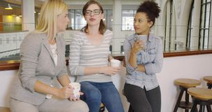 Women with coffee cups. Three attractive women in casual clothes sitting on bar stools during break, holding cups of coffee and having chat stock video