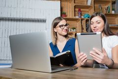 Women colleagues successful IT support specialists working with net-book and portable digital tablet stock images