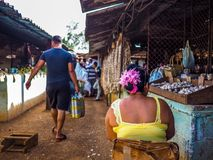 Women with colorful flowers on a cuban market. Shopping man passing by a women with bright colors on a cuban market in camaguey Stock Photo