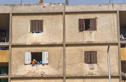 Women in colorful head scarves laugh out cement apartment window as a small boy looks down at them from above Stock Photography