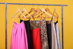 Women colorful skirts on hangers on  rack on orange background. Royalty Free Stock Photography
