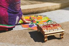 Women coloring traditional rice art pattern Rangoli for indian marriage rituals. Women coloring tradition colorful rice art or sand art Rangoli on the floor with Stock Photo