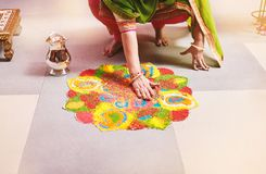 Women coloring traditional rice art Rangoli for indian marriage rituals. Women coloring tradition colorful rice art or sand art Rangoli on the floor with paper Royalty Free Stock Photos