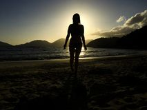 Women comes out of the sea. A curvy woman comes out of the sea in the sunset on a sandy beach royalty free stock photos