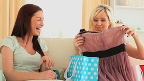 Women comparing content of their shopping bags. Girls comparing content of their shopping bags stock footage