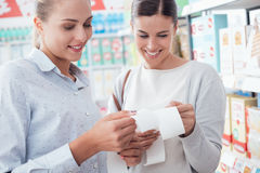 Women comparing their grocery receipts stock images