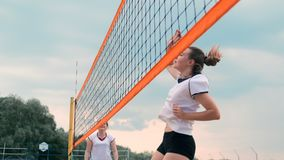 Women Competing in a Professional Beach Volleyball Tournament. A defender attempts to stop a shot during the 2 women. International professional beach stock video footage