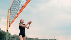 Women Competing in a Professional Beach Volleyball Tournament. A defender attempts to stop a shot during the 2 women. International professional beach stock video