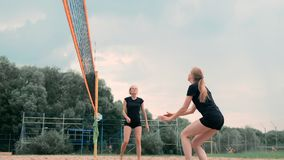Women Competing in a Professional Beach Volleyball Tournament. A defender attempts to stop a shot during the 2 women. International professional beach stock footage