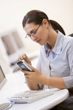Women by computer with digtial personal organsier Stock Images