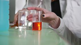 A women conduct an experement in medical laboratory. A women conduct an experement with orange liquid in medical laboratory stock video