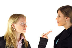 Women in Confrontation. Two young adult women in a confrontational pose.  Models are dressed in business attire and are isolated on white background.  Faces are Stock Photo