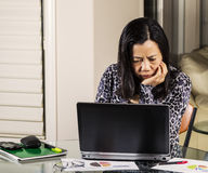 Women confused from information on computer. Mature woman looking confused at information on computer while working from home Stock Photography