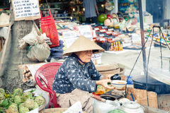Women in conical hat selling food. Hoi An, Vietnam - March 14, 2014: Women in conical hat selling food on fresh market on 14 March 2014, Hoi An, Vietnam stock images