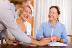 Women consulting at insurance agent. Happy mature women consulting at insurance agent office. Focus on the left woman Royalty Free Stock Photography