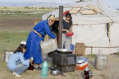 Women cook in front of the yurt entrance, circa Harhorin, Mongolia. Royalty Free Stock Image