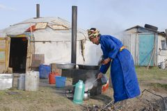 Women cook in front of the yurt entrance, circa Harhorin, Mongolia. Royalty Free Stock Photography