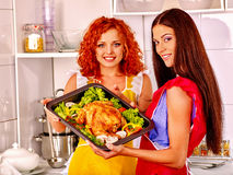 Women cooking chicken at kitchen Royalty Free Stock Image