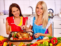 Women cooking chicken at kitchen Stock Images