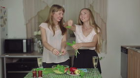 Women Cooking salad smiling on a Kitchen and Talking healthy food. Women Cooking Food on a Kitchen and Talking cut salad healthy food torn lettuce leaves stock video footage