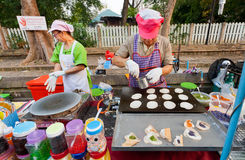 Women cooking small pancakes  on a stove during street fair with fast food court Royalty Free Stock Photography