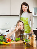 Women cooking something with vegetables. At kitchen. Focus on blonde stock photo