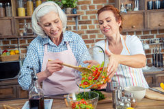 Women cooking together. Two smiling women cooking vegetable salad together Royalty Free Stock Images