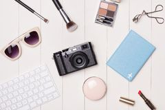 Women cosmetics and fashion items on table with camera and passport. Top view stock photos