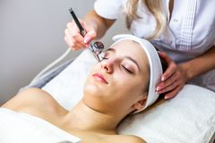 Women in cosmetology cabinet. Cosmetologist is doing procedure for young girl. Women in cosmetology cabinet. Cosmetologist is doing procedure for young woman Royalty Free Stock Image