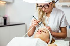 Women in cosmetology cabinet. Cosmetologist is doing procedure for young girl. Women in cosmetology cabinet. Cosmetologist is doing procedure for young woman Royalty Free Stock Photography