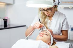 Women in cosmetology cabinet. Cosmetologist is doing procedure for young girl. Women in cosmetology cabinet. Cosmetologist is doing procedure for young woman Royalty Free Stock Photo