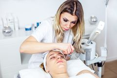 Women in cosmetology cabinet. Cosmetologist is doing procedure for young girl. Women in cosmetology cabinet. Cosmetologist is doing procedure for young woman Royalty Free Stock Images