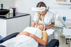 Women in cosmetology cabinet. Cosmetologist is doing procedure for young girl. Women in cosmetology cabinet. Cosmetologist is doing procedure for young woman Stock Photo