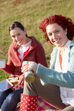 Women on country picnic. Smiling at camera Royalty Free Stock Images