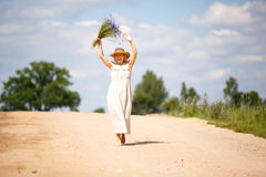 Women on country road with flowers royalty free stock photography