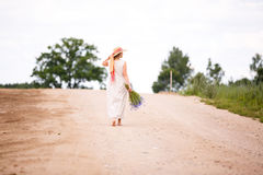 Women on country road with flowers Stock Photo